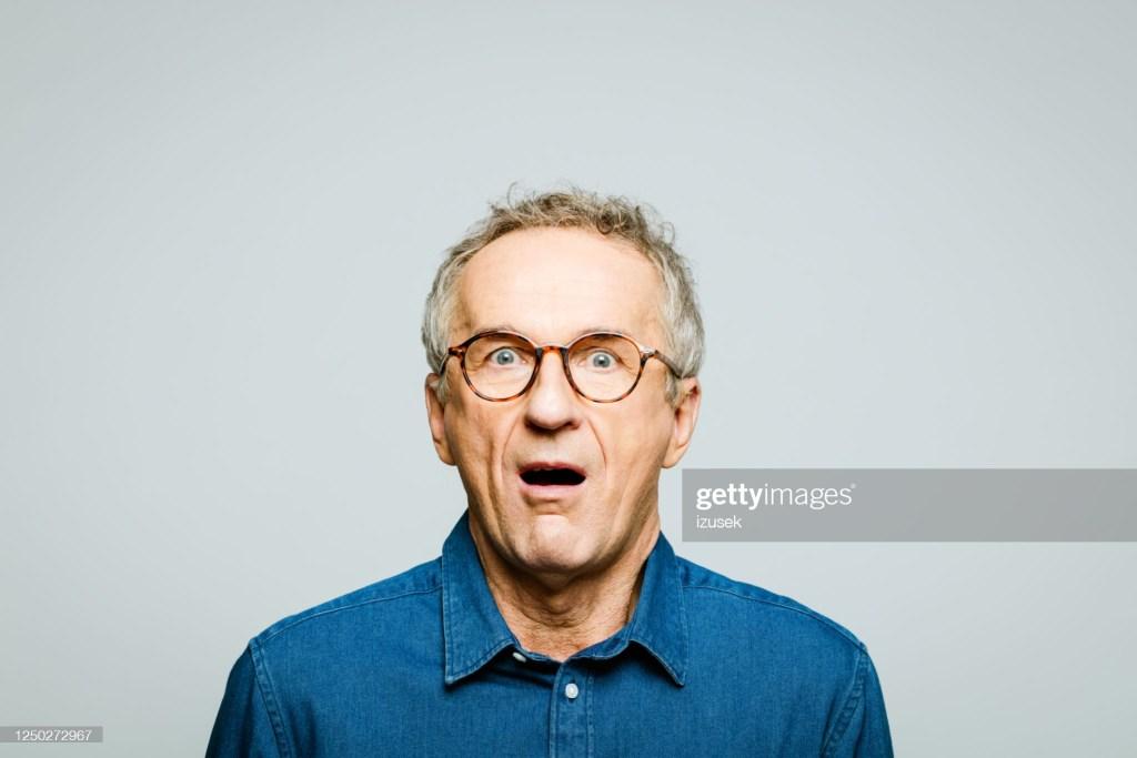 Portrait of elderly man wearing white denim shirt and glasses staring at camera with mouth open. Terrified senior entrepreneur, studio shot against grey background.