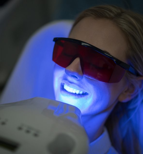 Beautiful woman at a spa getting teeth whitening with laser