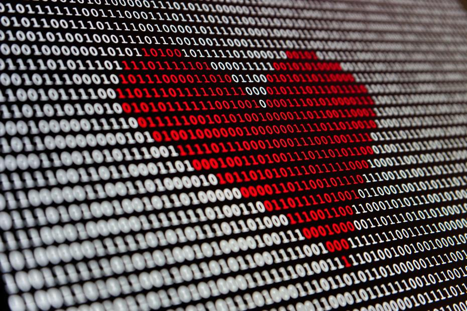 A heart in red digits stands out against a screen of white binary code.