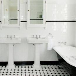Using a minimal black and white colour palette, this bathrom design features Art Deco era inspired bath fittings such as the elegant white pedestal basins and the black freestanding bathtub,.