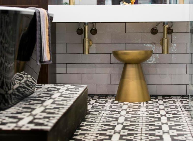 A bold patterned floor tile paired with the simple elegance of a white gloss subway wall tile. Include metallic finishes to inject the space with warmth, texture and luxury.