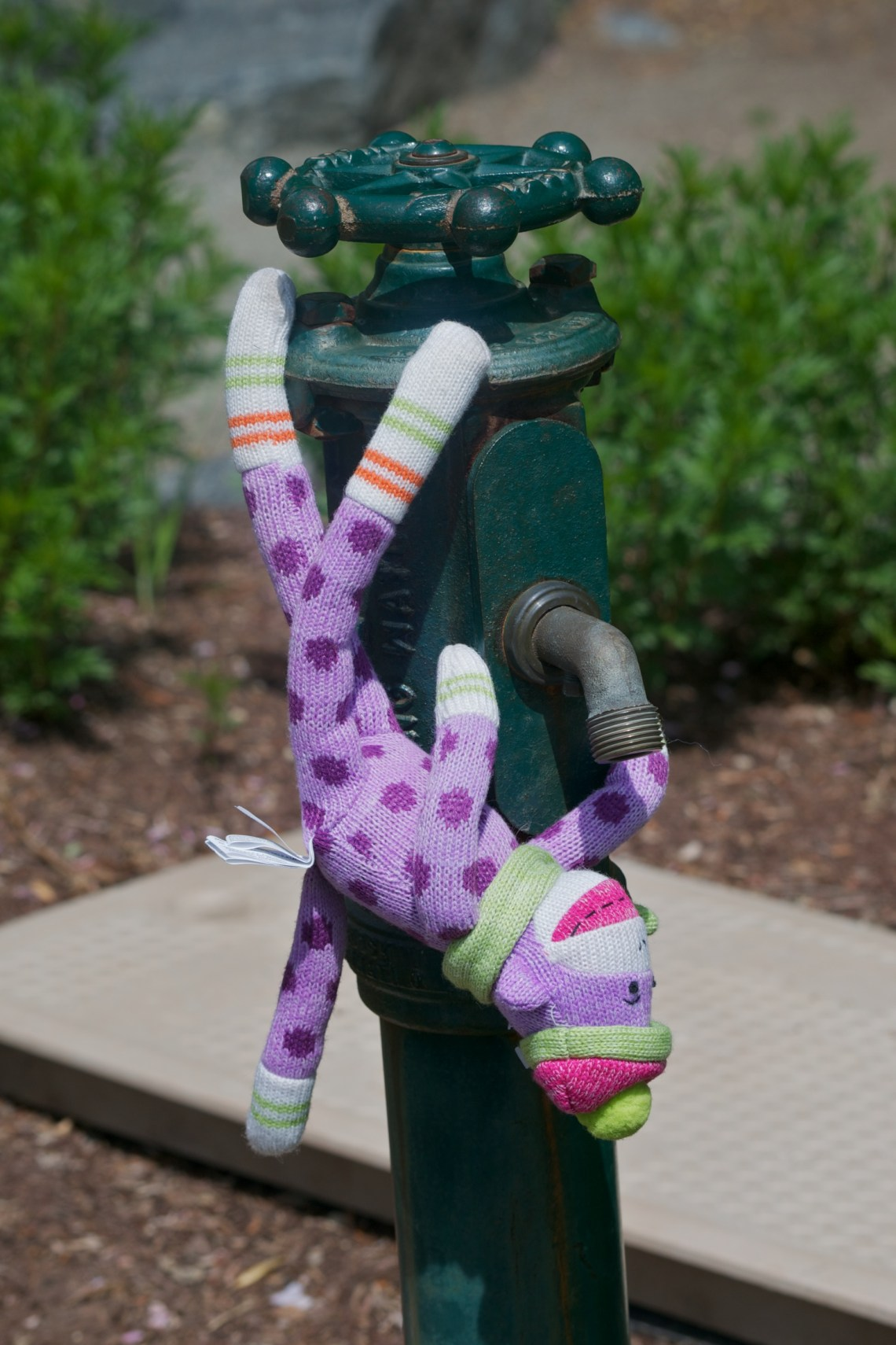 Sock Monkey Drinking from a Spigot