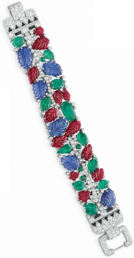 Art Deco tutti frutti bracelet, by Cartier, circa 1930. Designed as a meandering diamond vine, the barcelet is set with carved ruby, sapphire and emerald leaves, enhanced by emerald bead berries.
