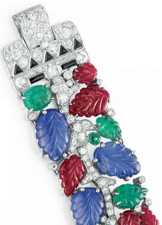 Clasp of an Art Deco tutti frutti bracelet, by Cartier, circa 1930. Designed as a diamond vine and set with carved ruby, sapphire and emerald leaves, and emerald bead berries.