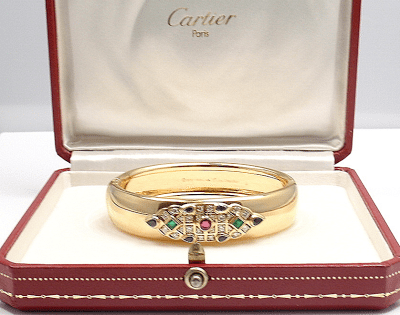 Cartier diamond and gem-set bracelet. Set with one round-cut ruby; two square-cut emeralds; four pear-shaped sapphires; and 24 round brilliant cut diamonds, VS clarity, G color. Total diamond weight is 1.50 carats.