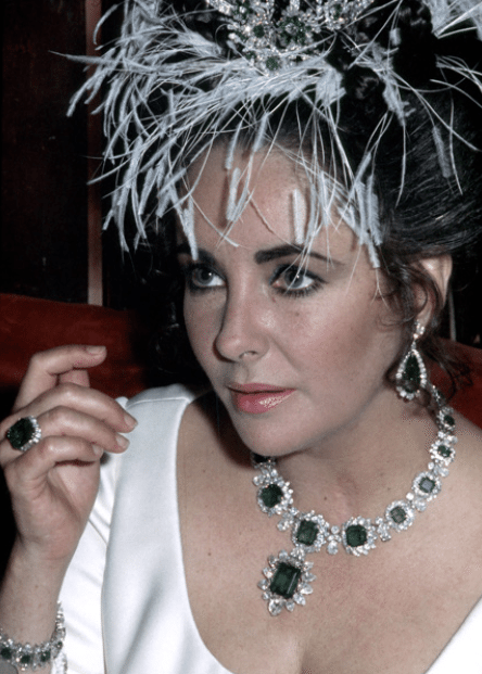 Elizabeth Taylor with her Bulgari emerald and diamond suite. Via Diamonds in the Library.