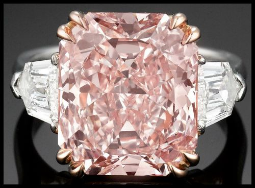7.09 carat type IIa fancy pink diamond flanked on either side by two shield or bullet-cut diamonds, totaling 1.04 carats and both graded E color and VS1 clarity. Via Diamonds in the Library.