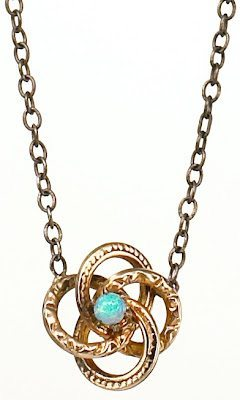 Love knot pendant from the Estate of Grace Collection. This pendant was originally a Victorian stickpin. The 14k gold love knot centered by a vibrant opal is suspended from an oxidized sterling silver chain.
