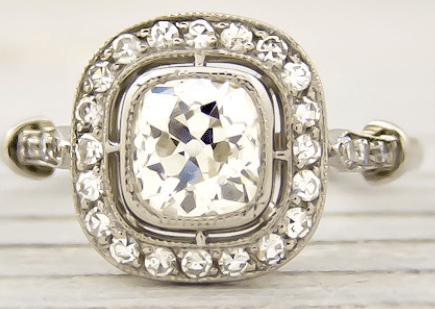 Reproduction of an early Art Deco engagement ring. Featuring a .70 carat old European cut diamond, encircled with single cut diamonds. Via Diamonds in the Library.