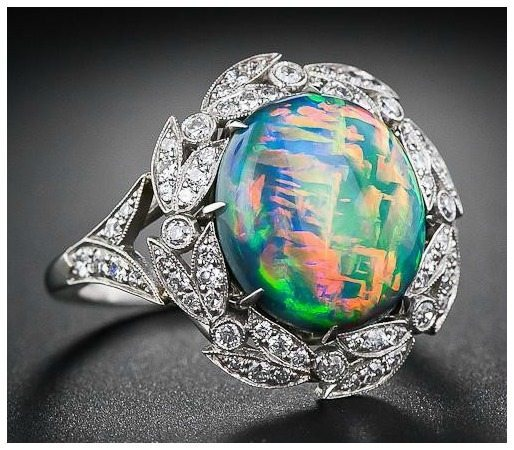 Tilted front view; a fire opal and diamond ring. Via Diamonds in the Library.