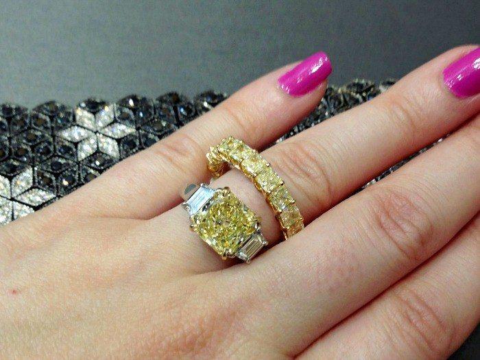 A yellow diamond and diamond engagement ring, yellow diamond eternity band, and black diamond and white diamond bracelet, all by Sasha Primak. Via Diamonds in the Library.