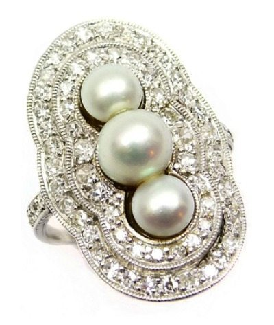 Three stone pearl and diamond cluster ring, circa 1905. Millegrain set in platinum, with diamonds to the shoulders. Via Diamonds in the Library.