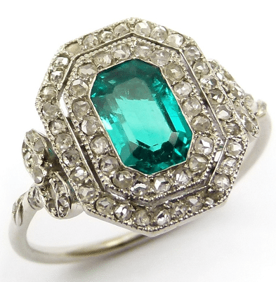 Antique Belle Époque emerald and diamond cluster ring with a trap-cut emerald is set with rose diamonds. Outside of the double halo, the ring has bow-shaped, diamond-set shoulders.