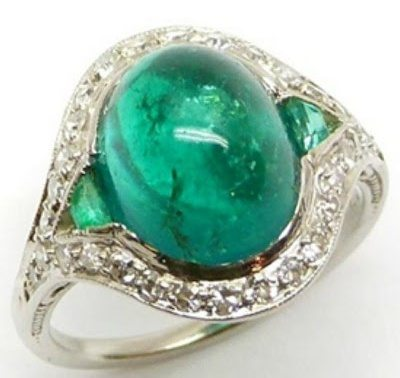 Art Deco emerald and diamond ring, circa 1930. The center stone is a large, oval cabochon-shaped emerald flanked by tapered baguette emeralds and with a diamond set border.