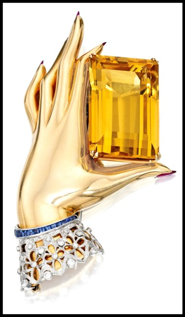 Brooch, circa 1940. A gold hand with ruby cabochon fingernails pinches a 100 carat citrine between thumb and forefinger before disapearing at the wrist into a delicate lace cuff detailed in diamonds and calibré-cut sapphires. Via Diamonds in the Library.
