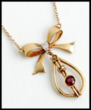 Rose Gold Art Deco lavaliere necklace with garnet, bow, and floral accent