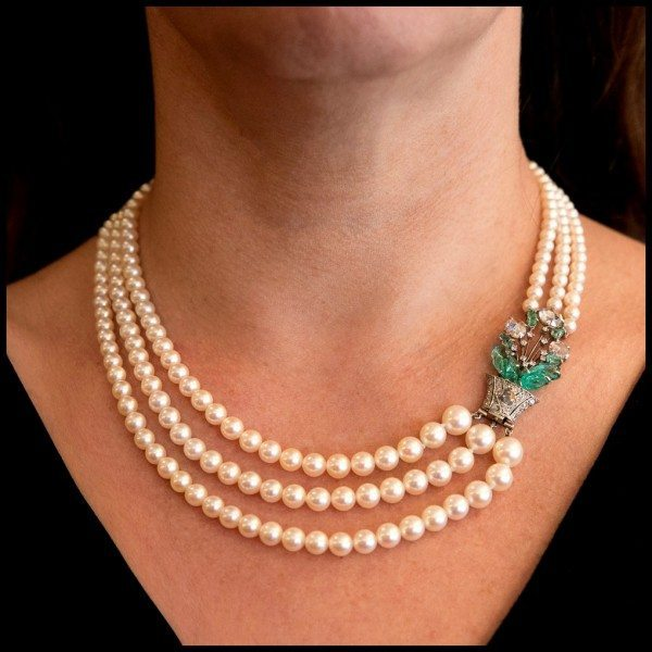 Art Deco Boucheron pearl necklace with three strands of pearls and a floral clasp with carved emeralds and rose cut diamonds. At Lang Antiques.