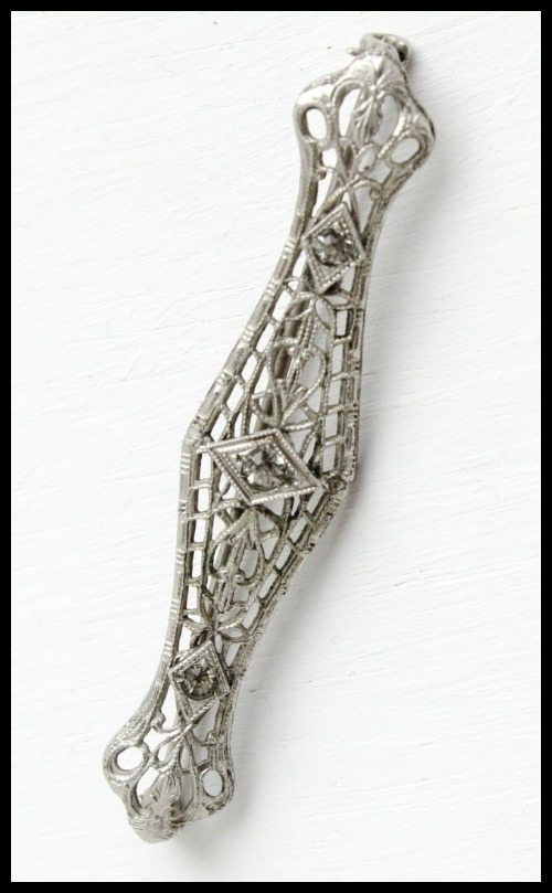 Antique Art Deco brooch with rhinestone and silver tone filigree.
