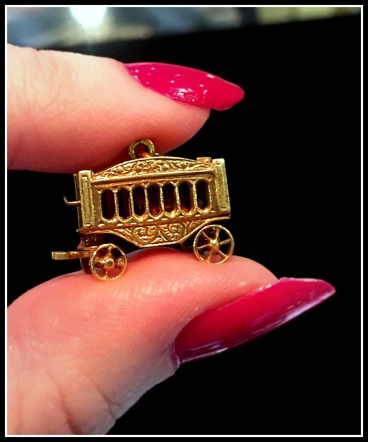 Antique gold charm designed in the shape of a tiny circus wagon with tiny, working wheels and a tiny gold lion inside.