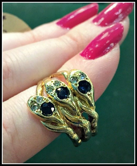 Antique triple snake ring with diamonds and sapphires in gold.