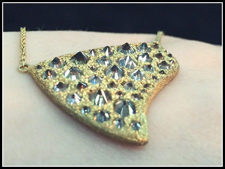 Side detail of a TAP by Todd Pownell gold pendant with pavillion-up diamonds.