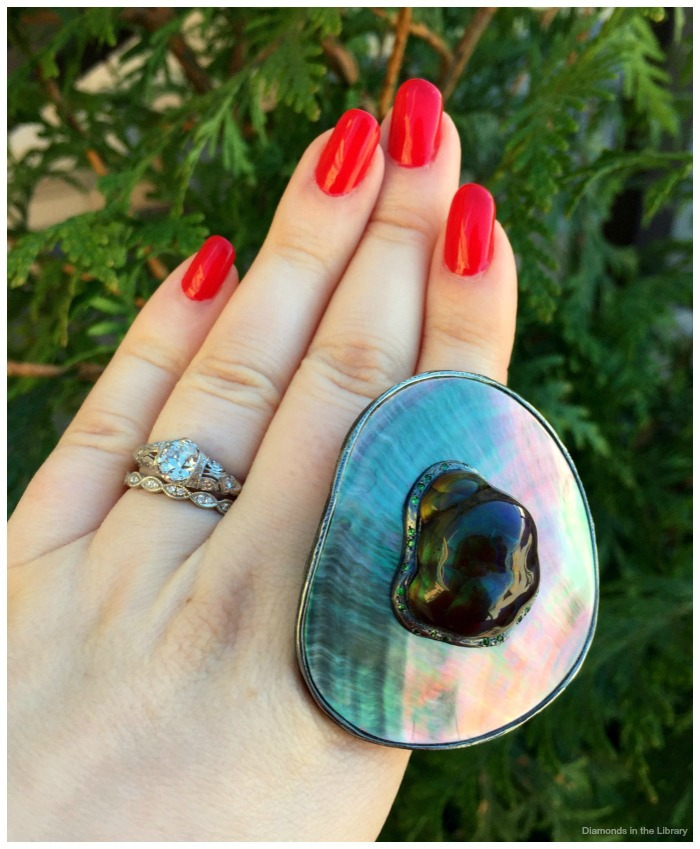 By Jennifer R. Morin of Gregore Joilliers, this sterling silver ring features a 30.70 ct fire agate cabochon set in mother of pearl with green garnets.