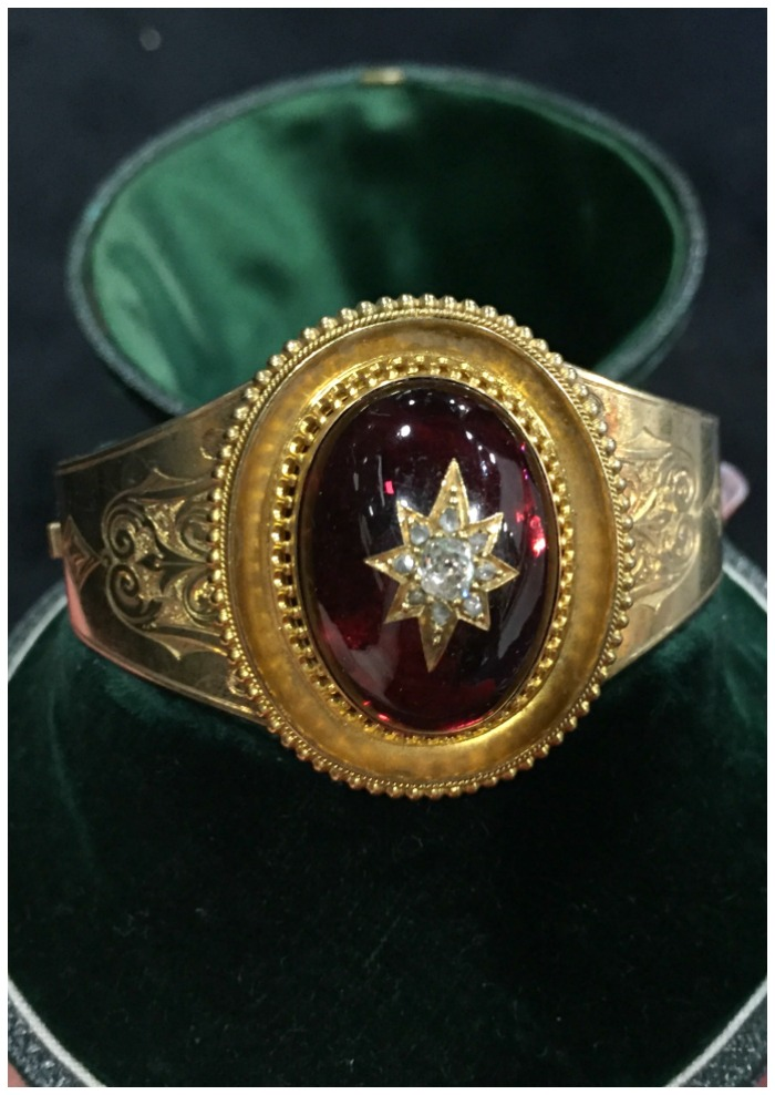 A beautiful Victorian gold cuff bracelet with a huge cabochon garnet inset with a diamond star. At Cynthia Findlay Antiques.