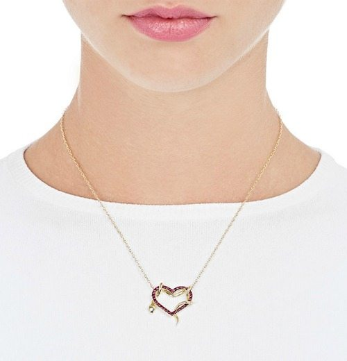 A heart and snake pendant necklace by Finn. In gold, with ruby pave on the heart and diamond eyes on the snake.