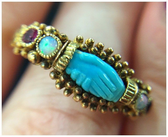A rare and exceptional antique ring with gold detailing and a turquoise carving showing a clasped pair of hands. At Spare Room Antiques.