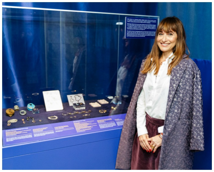 Marla Aaron standing in front of an exhibit on gold at the Museum of American Finance which includes a number of pieces of her work.