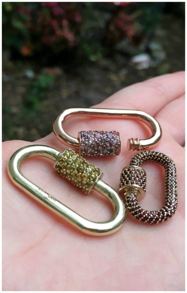 Three gold Marla Aaron locks with gemstones