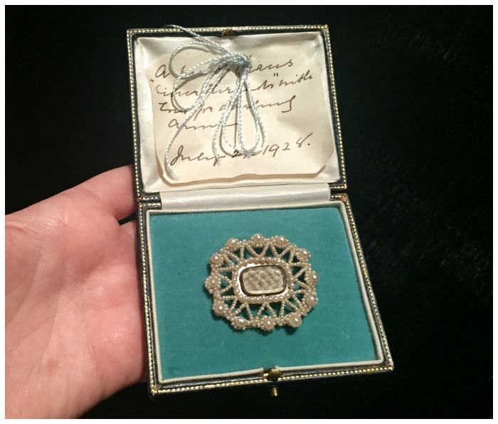A beautiful late Victorian mourning brooch in a box with a note sewn in. The is dated 1928, and says the hair in the brooch is from her grandmother. At Lowther Antiques.