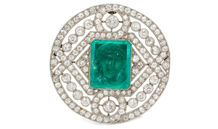 A Platinum, Diamond and Emerald Cameo Brooch, with a classical female profile depicted on a step-cut emerald.