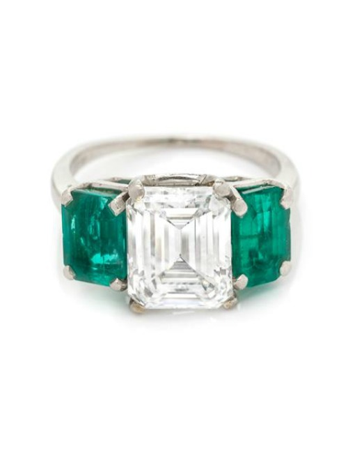 A Platinum, Diamond and Emerald Ring, containing one octagonal step cut diamond weighing approximately 3.07 carats and two octagonal step cut emeralds weighing approximately 2.00 carats total.