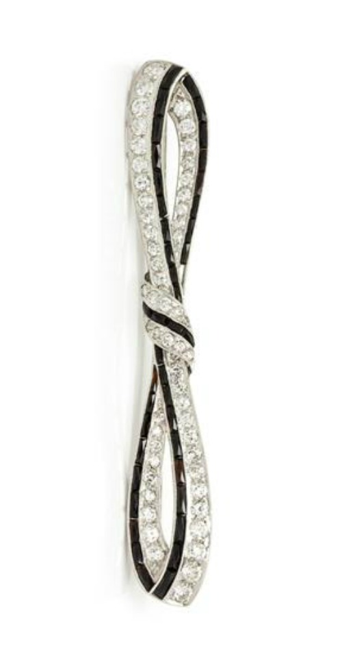 An Art Deco Platinum, Diamond and Onyx Bar Brooch, in a knotted ribbon motif, containing 56 diamonds (1.65 carats) with calibre cut onyx, double gallery with piercework.
