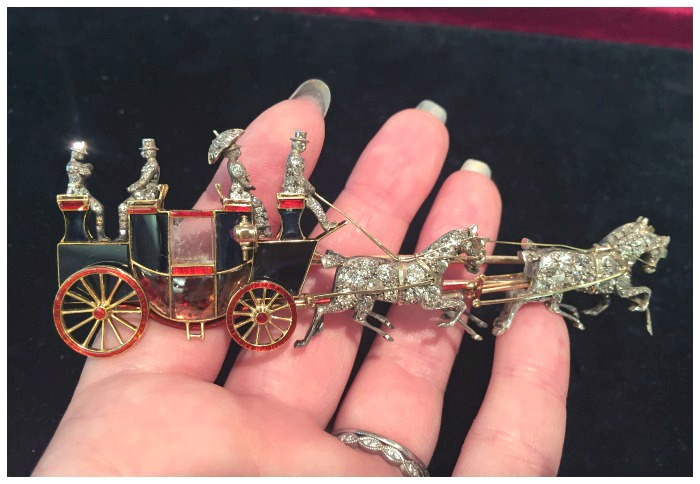 An incredible antique Victorian era brooch of a coaching scene, held in my hand for scale. Circa 1880, at SJ Shrubsole. In original box.