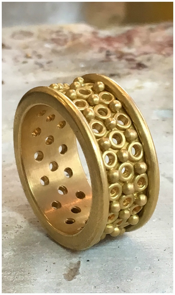 The Reinstein Ross Persian screen ring in yellow gold.