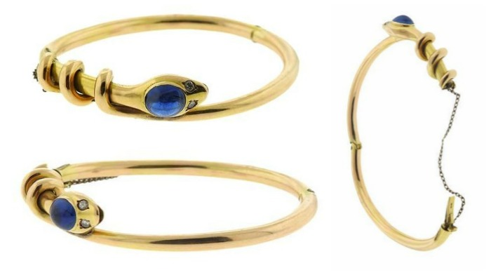 An antique Russian snake bangle in 14K yellow gold with diamond eyes and a sapphire cabochon.