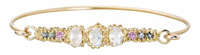 A beautiful handmade cuff bracelet by Ruta Reifen, with sapphires, rubies, and rainbow moonstone gemstones.