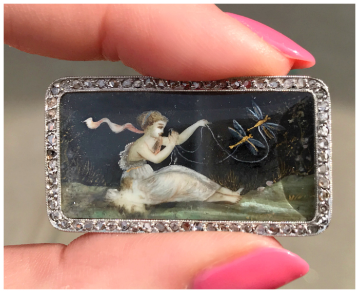 This beautiful antique brooch contains a painting of a girl in classical dress flying two dragonflies on delicate leashes made of ribbon. Spotted at Joden.