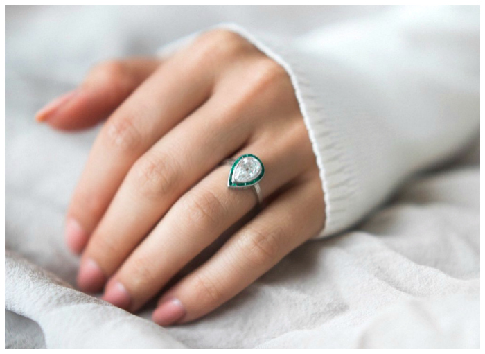 This beautiful engagement ring was made out of an antique brooch! It centers a1.57 carat antique pear cut diamond bezel set in platinum and surrounded by a halo of calibre cut emeralds.