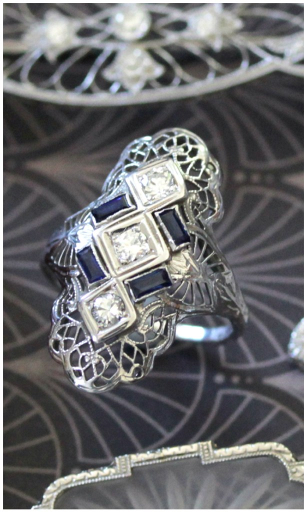 A lovely sapphire and diamond ring from the Art Deco era. Look at that lovely filigree! This antique beauty is Art Deco era.