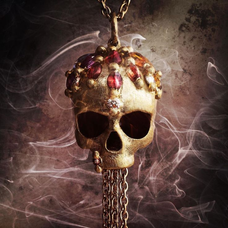 An incredible skull necklace by Polly Wales. In gold with bright gemstones.