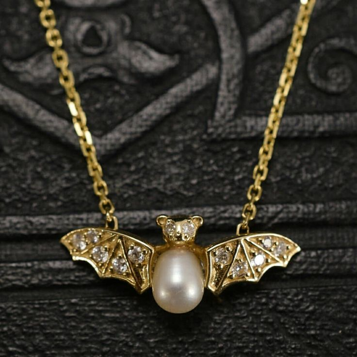 I love this bat necklace! Pearls and diamonds in gold, from Erica Weiner.