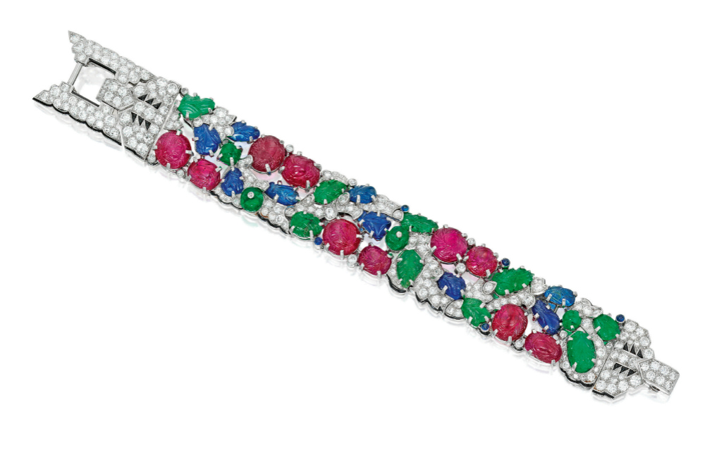 A rare and beautiful Cartier Tutti Frutti bracelet; Art Deco era, circa 1930. Diamonds with carved rubies, emeralds, and sapphires. Flat lay.