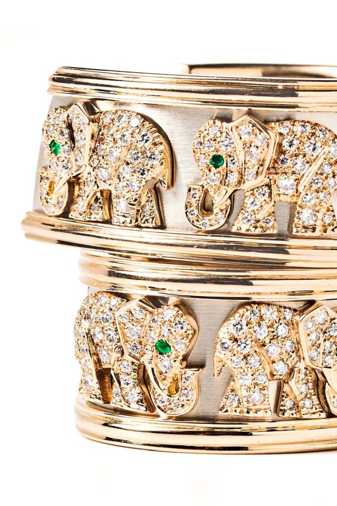 Close up of a pair of gold Cartier earrings with walking elephants in diamonds and emeralds. From Tiina Smith.