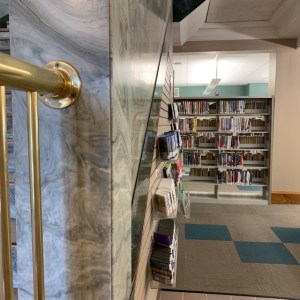 stepping inside the library, green and white marble walls, book cases , brass rail