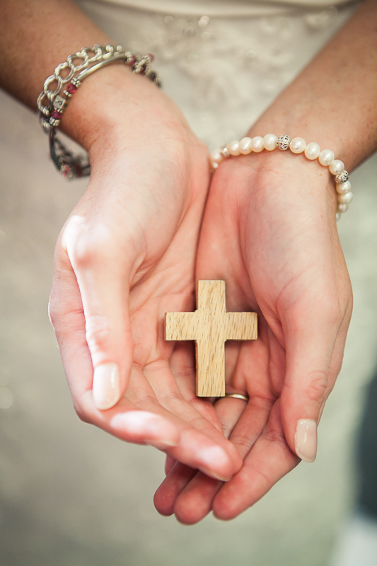 brides hands holding cross