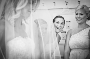 bridesmaids smiling at veiled bride at st luke's chapel