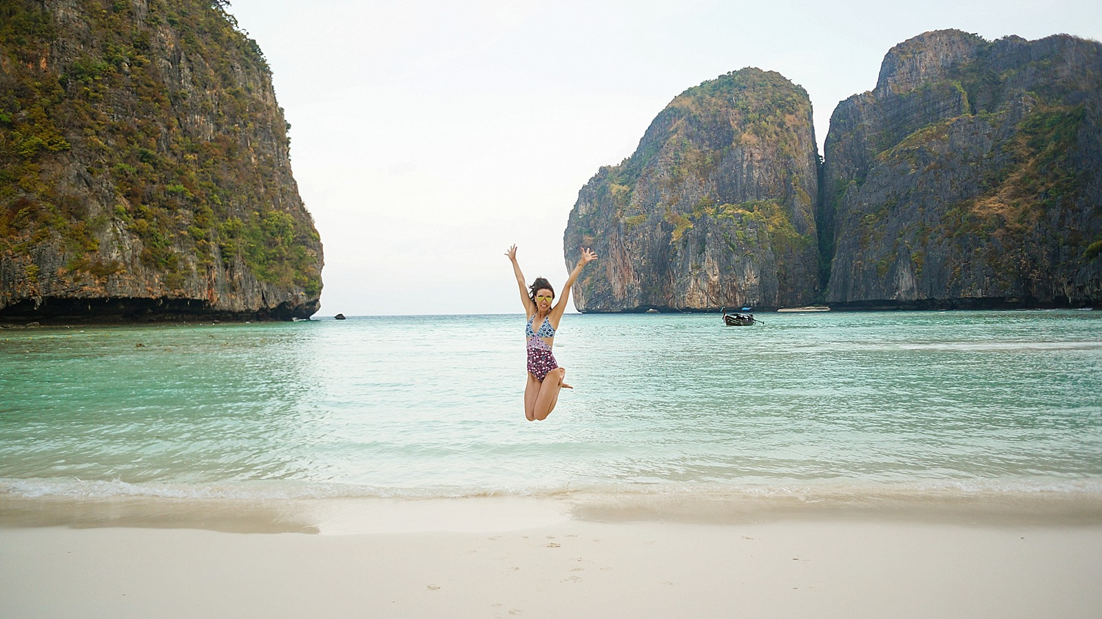 diana elizabeth blogger in Koh phi phi island Maya bay jumping in sand with hands up in the air